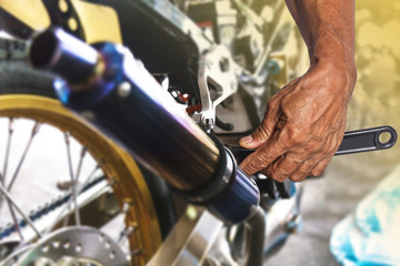 Hand with wrench, Professional mechanic repair and modifications to motorcycle