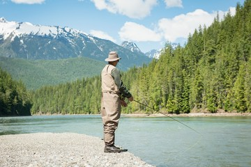 Full length of man fishing in river while standing on riverbank