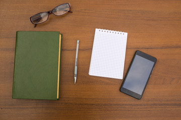 Book, notepad, pen, eyeglasses and smart phone on wooden desk