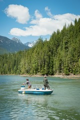 Male friends fishing while standing on boat in river