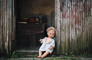 The old doll is left in the doorway of an old abandoned building. Fear of loneliness. Vintage background.