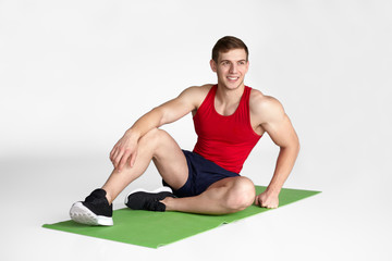 Fit man sitting on mat