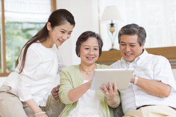 Senior couple and daughter looking at digital tablet