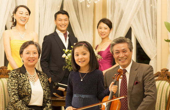 Girl holding the violin and smiling family