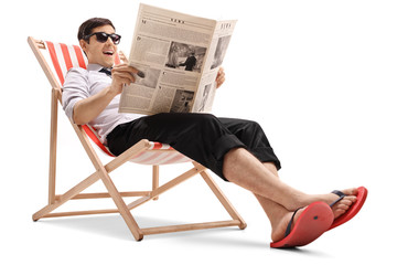Businessman sitting in a deck chair and reading a newspaper