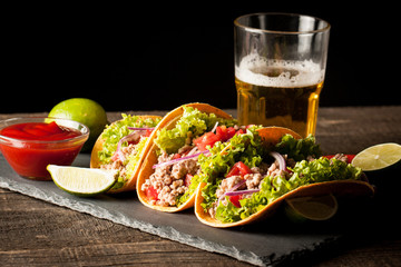 Photo of Mexican tacos with ground meat, beef, beans, onions and salsa on wooden background. Ketchup sauce and lime. A glass o beer in the background.
