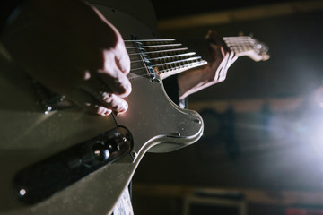 Playing electric guitar in studio closeup. Unrecognizable guitarist, music recording process, dark atmosphere with back light