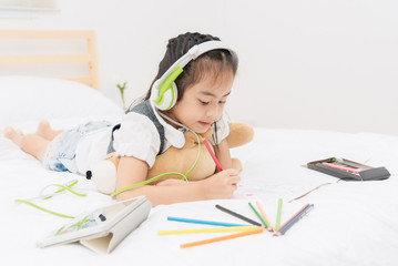 Little girl listen to music from headphone while drawing picture.