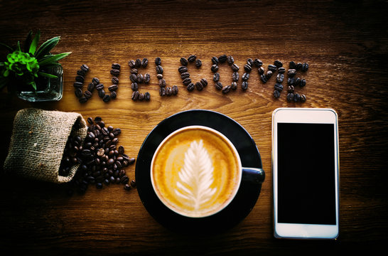 Welcome,written from coffee beans,smartphone on wooden.