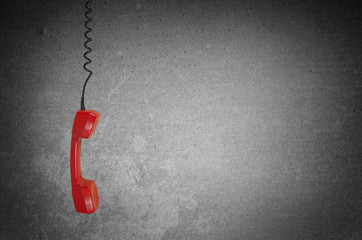 Red telephone receiver over gray background with copy space