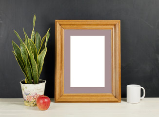 Mock up of blank photo frame with plant pot, mug and apple on wooden shelf.