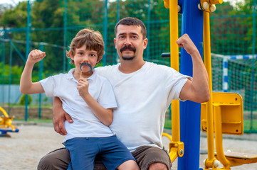 Father and son on the sports ground show strength