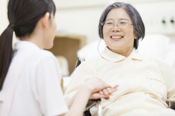 Nurse touching patient's hand in wheelchair