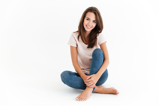Happy brunette woman sitting on floor and looking at camera