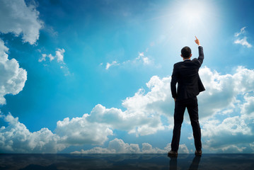 Back of successful businessman pointing up with his finger standing on top of building with sunlight sky background. Young man reaching goals, success and achievement concept. Copy space.