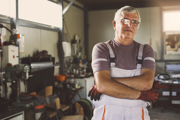 Senior man in workshop.  Man poses a crossed arm in a workshop and looks at the camera