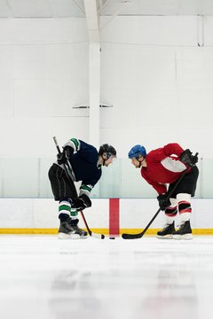 Side view of ice hockey players looking face to face