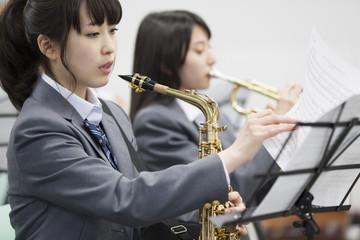 Female student turning over music score in music room
