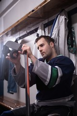 Male player taping hockey stick and puck in locker room
