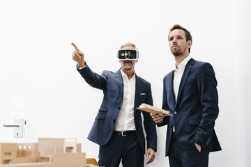 Two businessmen with VR glasses and architectural model