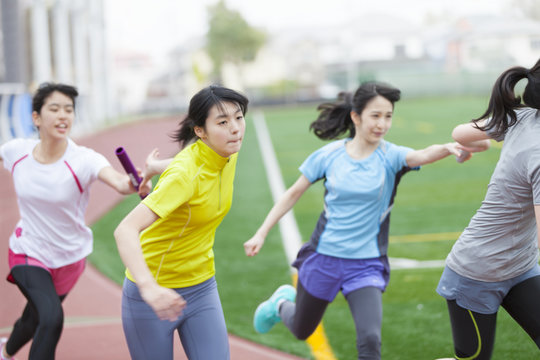 Female students on athletic trackpassing batons
