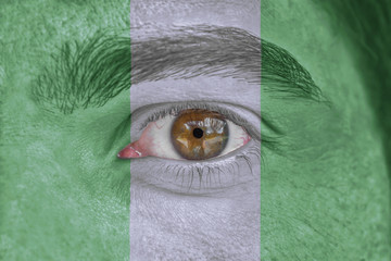 Human face and eye painted with flag of Nigeria