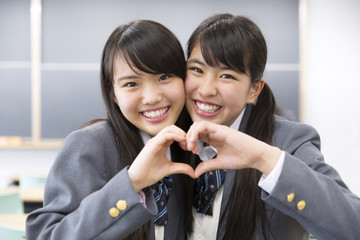 Two high school girls in a classroommakeing heart shape by hand