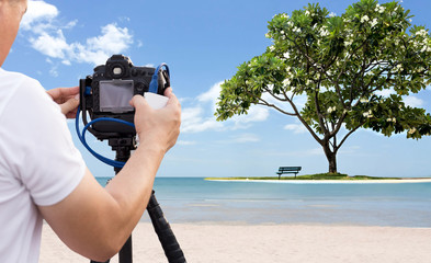 Photographer taking picture of the beach with frangipani tree