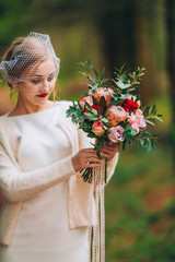 bride with flowers in hand outdoors.