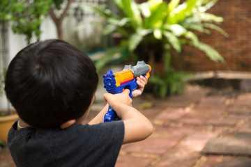 Little boy playing with a toy gun