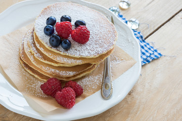 Tasty pancakes with forest fruits and powdered sugar