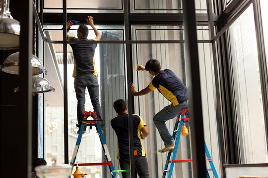 Unidentified worker applying tinted layer on glass window