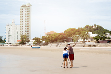 Couple taking picture using tripod on the beach