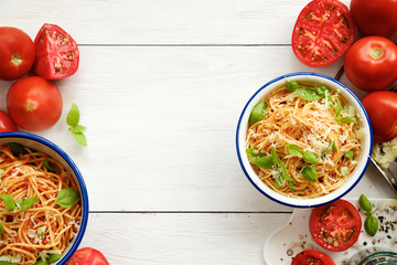Pasta with tomato and basil in bowls on white wooden background