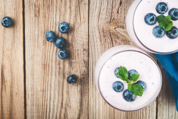 Smoothie or milkshake with  blueberries  in a glasses on rustic wooden  table, top view