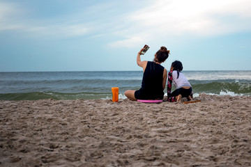 Mother and daughter enjoying vacation taking picture on cell phone by the beach