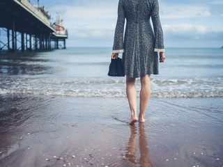 Woman walking on beach with shoes in hand