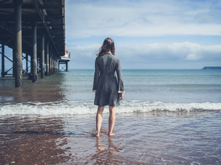 Young woman standing by a pier on the beach