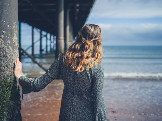 Young woman standing under pier