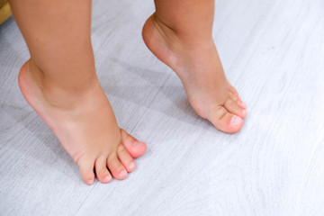 Children's bare feet. Child's bare feet on the wooden floor