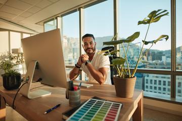 Handsome male entrepreneur sitting at his desk
