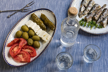 Two glasses and bottle of traditional drink Ouzo or Raki and appetizers on blue matting
