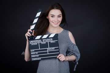young woman holding a clapperboard cinema