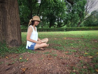 The lady with woven hat is reading book under big tree in a park.