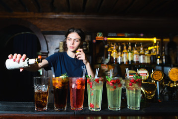 The barman creates beautiful and delicious alcoholic cocktails. Many beautiful alcoholic cocktails at the bar stand. Armenian pours alcohol into a cocktail