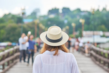 Asian women between the ages of 25-30 years, golden hair standing in a white hat in the middle of the bridge.