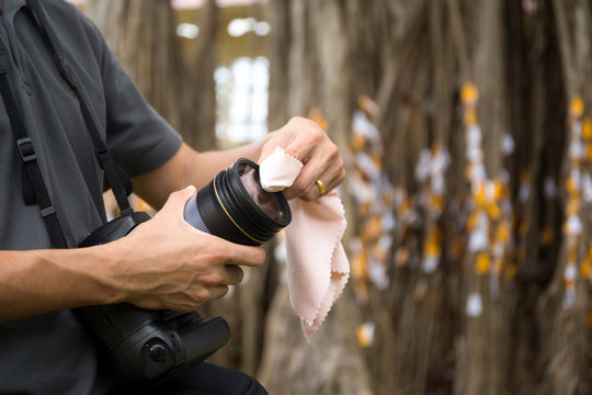 Photographer cleaning a camera lens with a micro