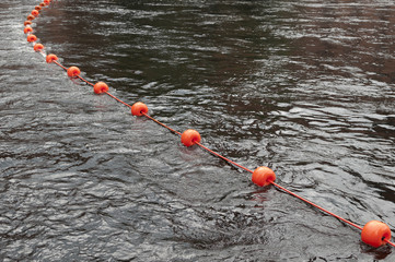 Red buoy floating in streaming water