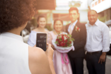 Woman taking picture of groom and bride with guest on cell phone