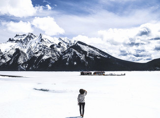 Rear view of woman looking at view while standing by frozen Lake Minnewanka against cloudy sky